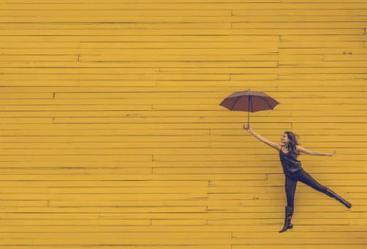 En av många gratis bilder på nätet - i detta fallet en kvinna som håller ett paraply mot en gul bakgrund.