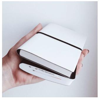 Reshot. Bild på vit och svart anteckningsbok.